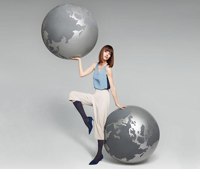 Junge Frau in ITEM m6 Reisstrümpfen und zwei Weltkugeln