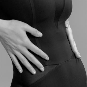 Detail einer jungen Frau in einem ITEM m6 Body mit den Händen an der Taille