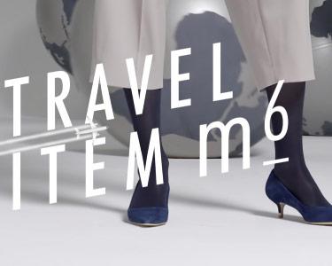 Beine einer Frau in ITEM m6 Reisestrümpfen und einer Weltkugel im Hintergrund