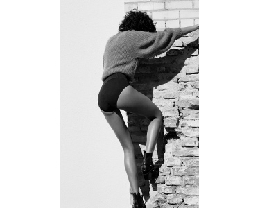 Young woman in ITEM m6 Shape Shorts climbing on a wall