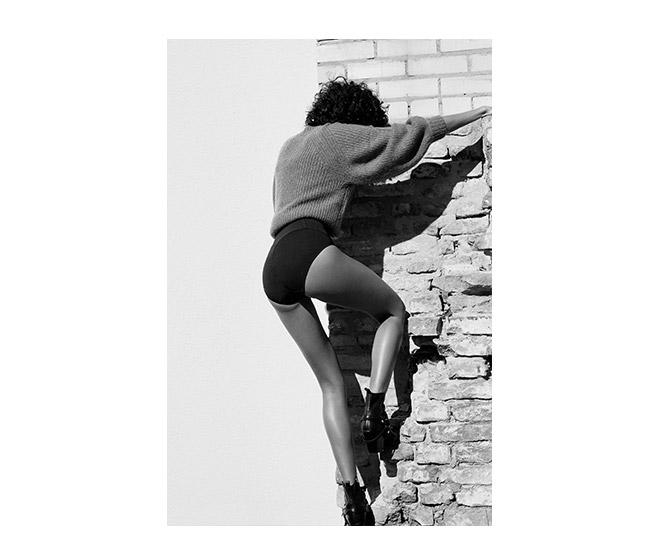 Junge Frau klettert in ITEM m6 Shape Shorts an einer Wand