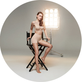 A woman wears the ITEM m6 Hollywood Contouring Tights and stands in the spotlight.